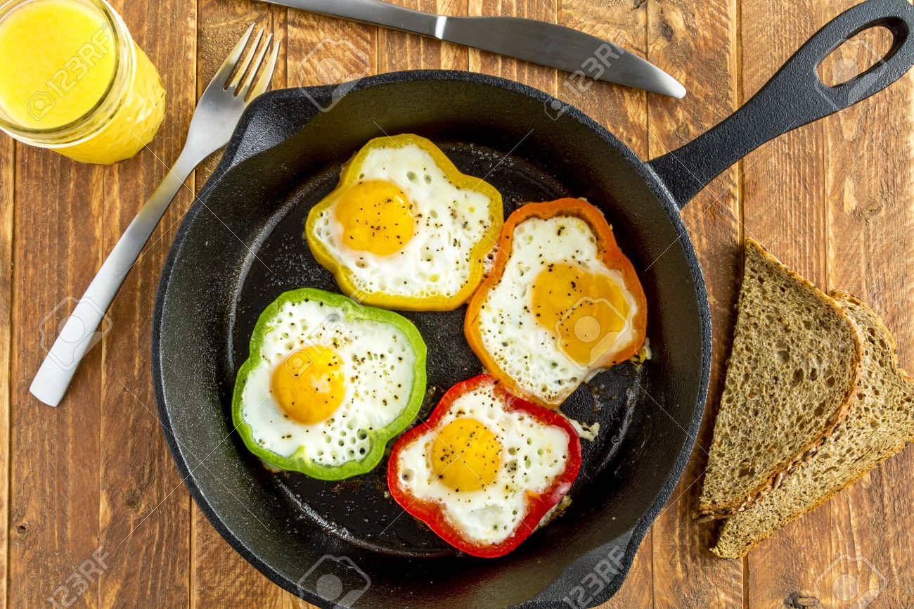 large cast iron skillet with fried eggs in green yellow red and orange bell
