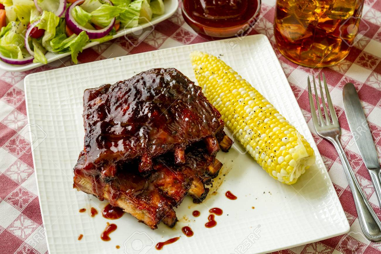 Picnic table setting with plate of bbq pork ribs with corn on the cob salad & Picnic Table Setting With Plate Of Bbq Pork Ribs With Corn On ...