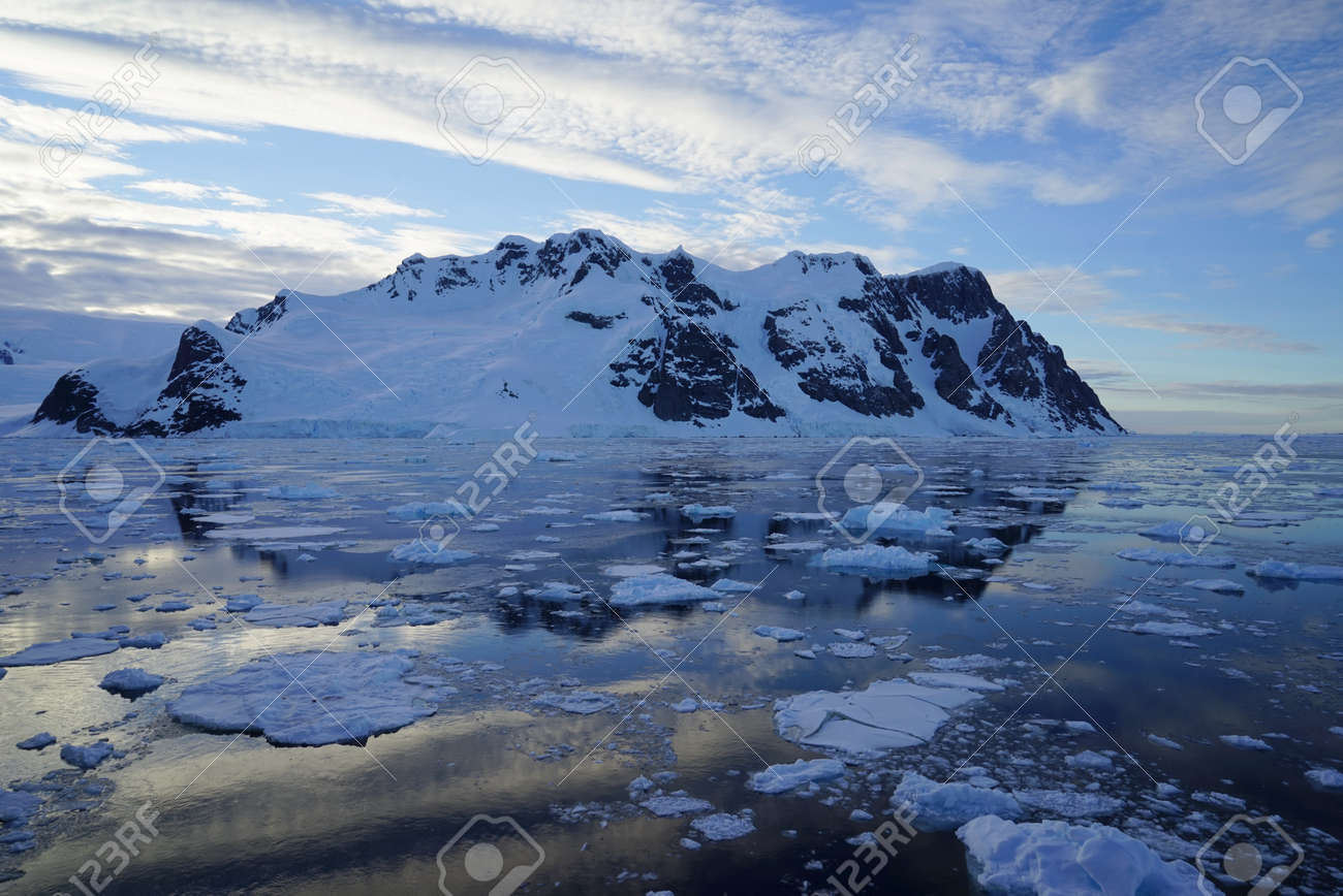This is summer in Pleneau Island, Antarctic Peninsula. There are penguins, whales, icebergs, ice floes, glaciers, oceans, radioactive clouds and sunlight. - 159771433
