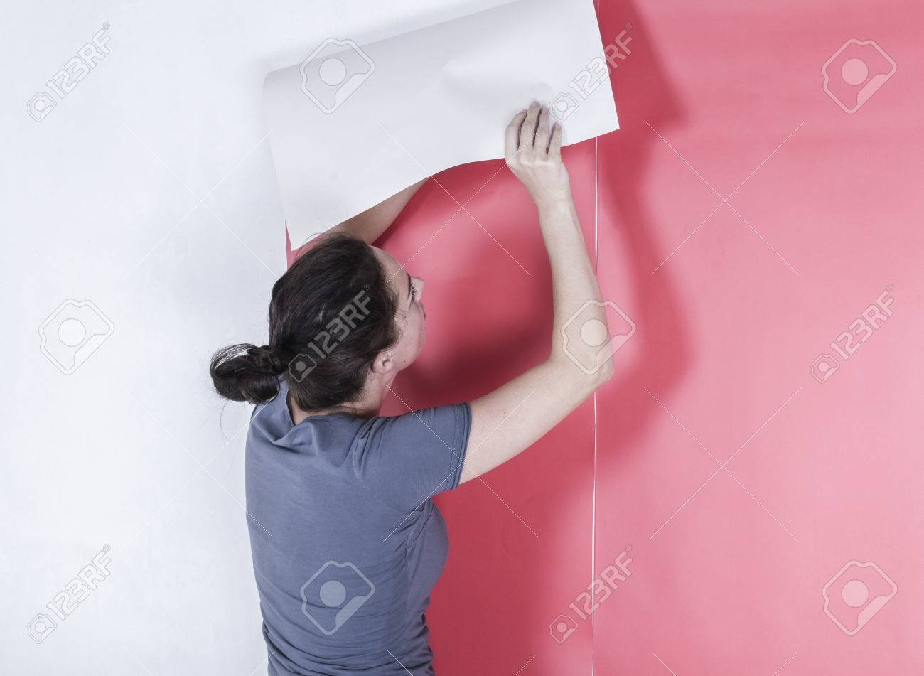 Woman hanging wallpaper Decorating the wall - 26249592