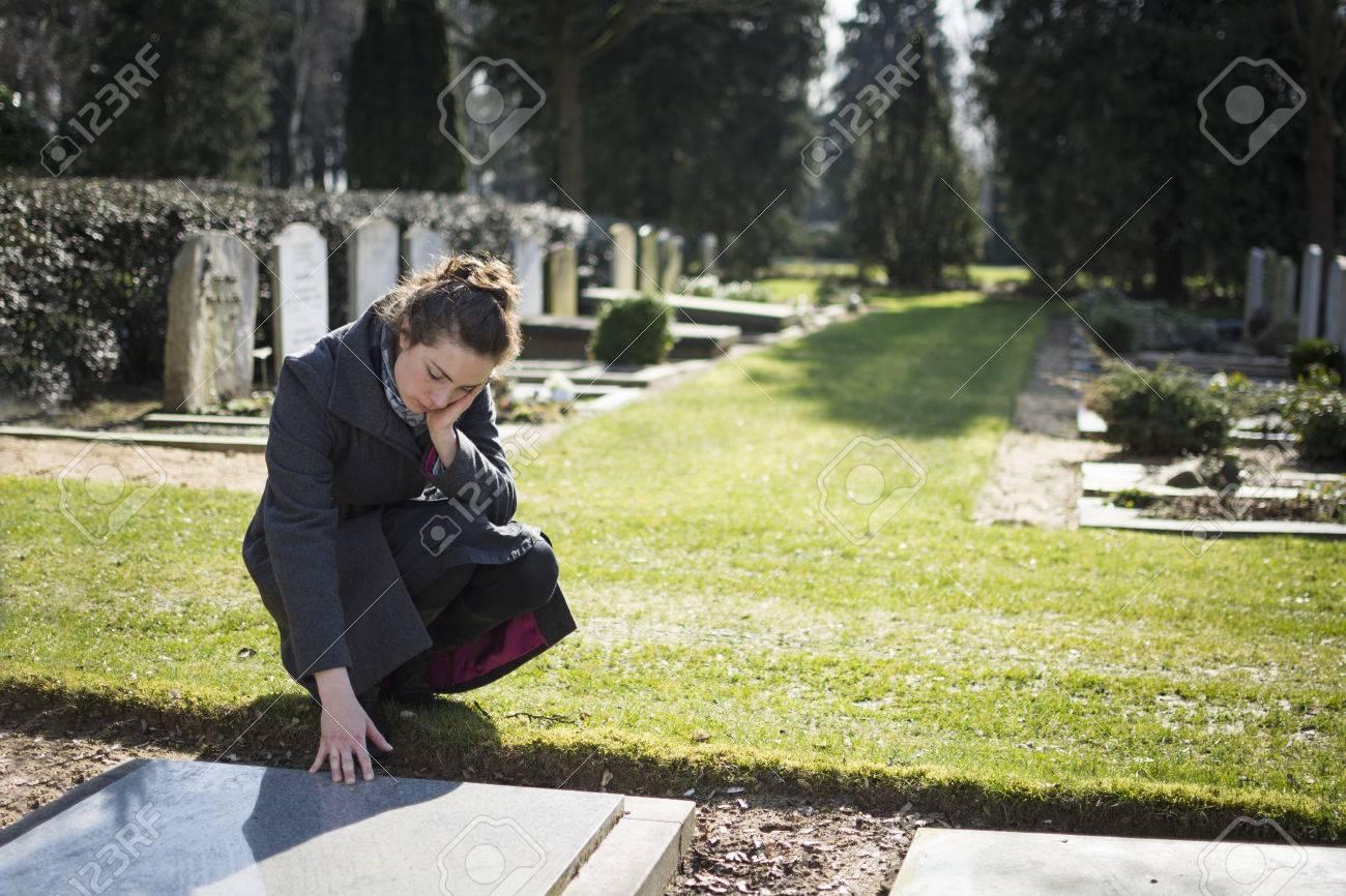 Woman sitting at gravestone on graveyard - 26559182