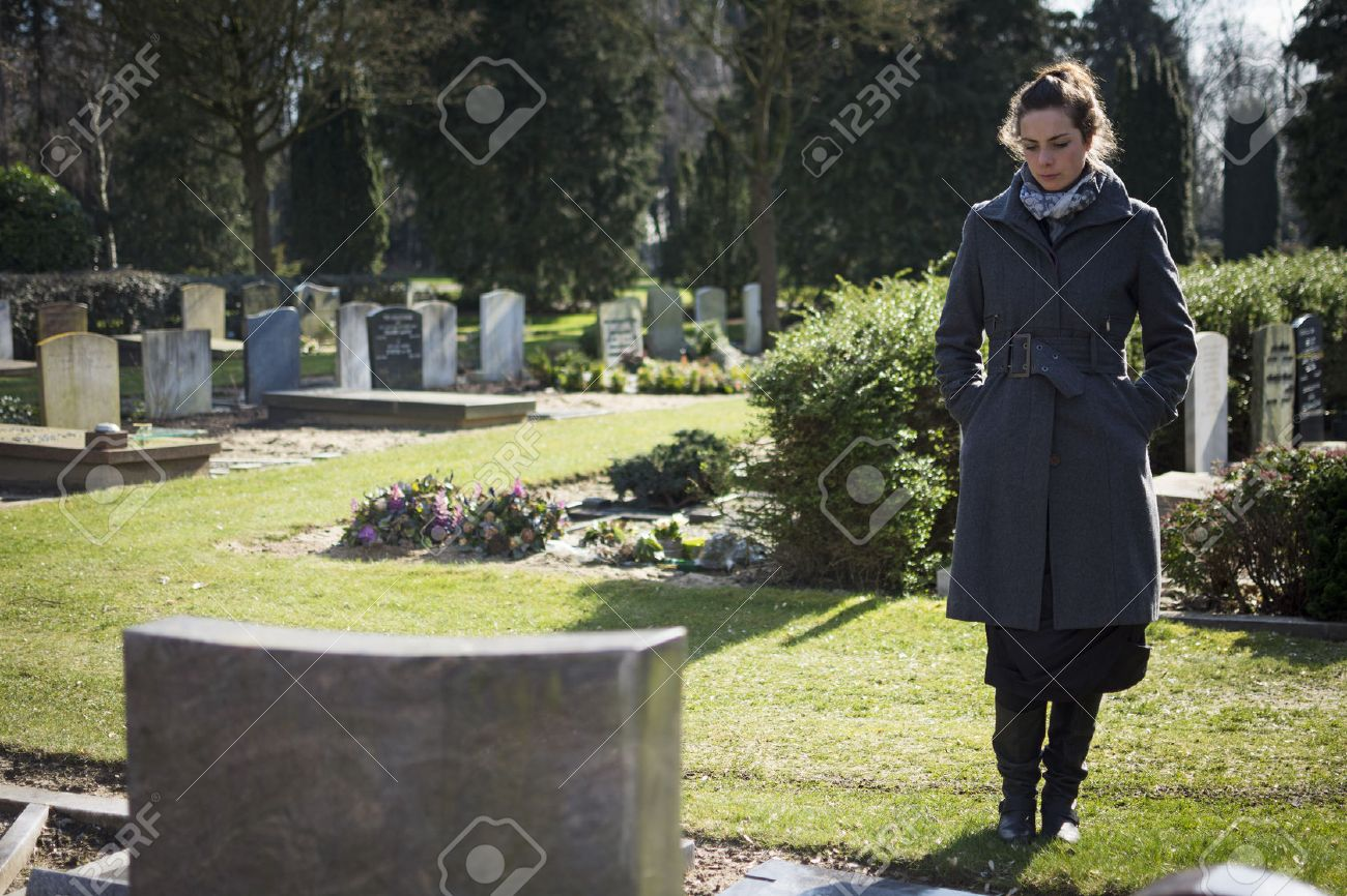 Widow standing at graveyard looking at grave - 26559211