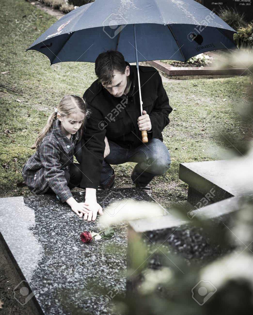 Father and child sitting at gravestone on graveyard - 26592866