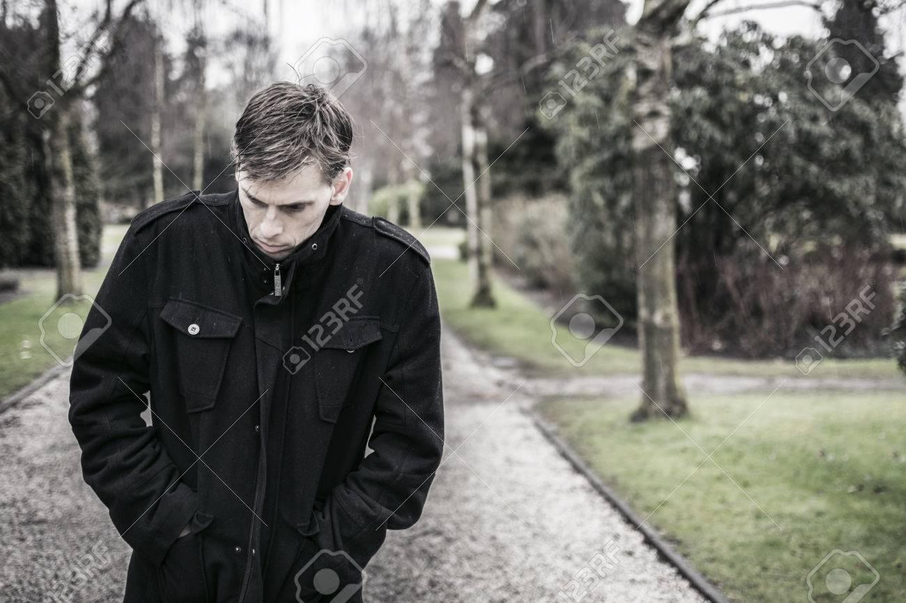 Depressed man walking outdoors Sad and troubled mind - 26559176