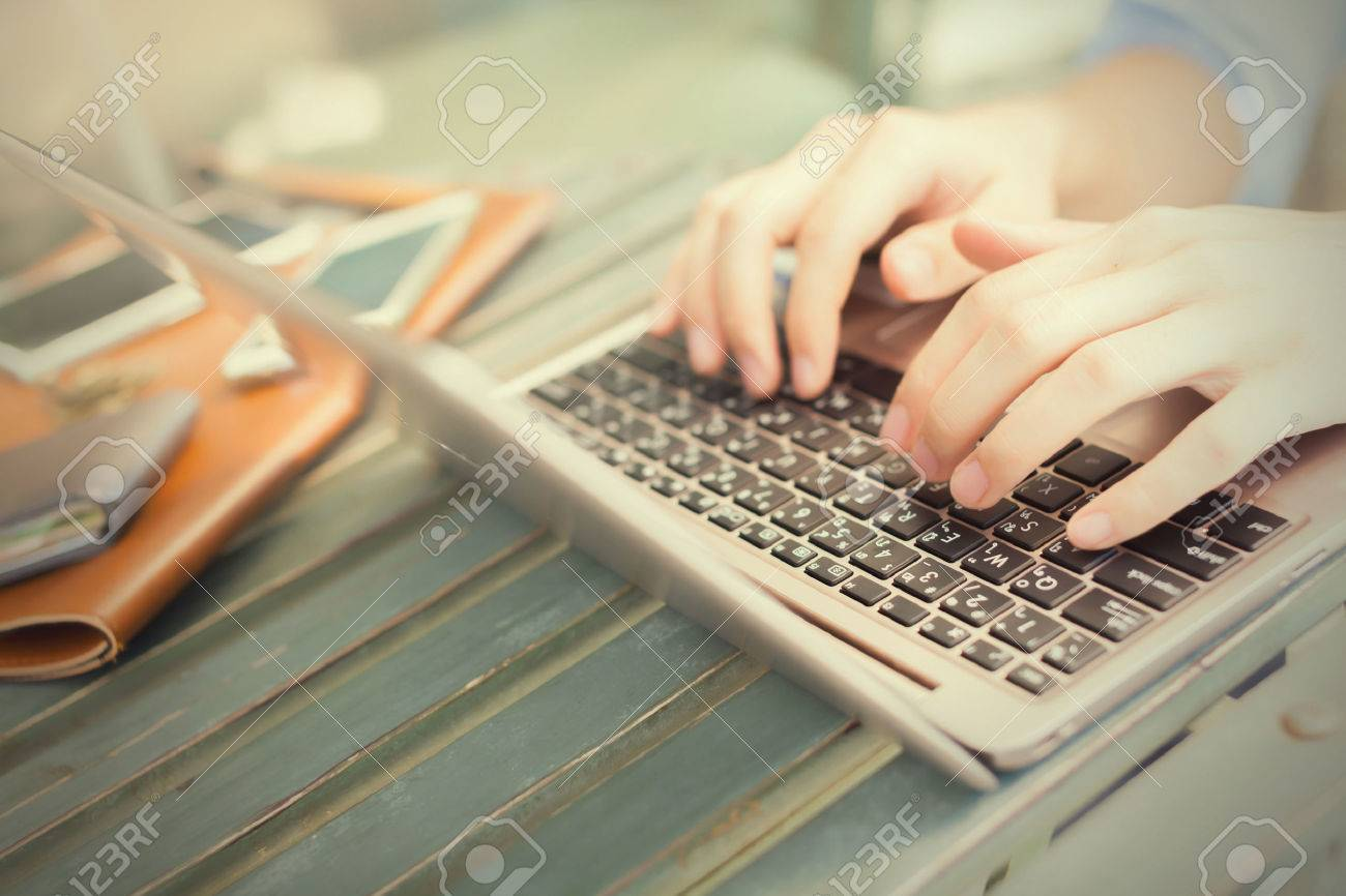 Hands typing on laptop and smart phones on his side - work anywhere concept (selective focus) Stock Photo - 50919781