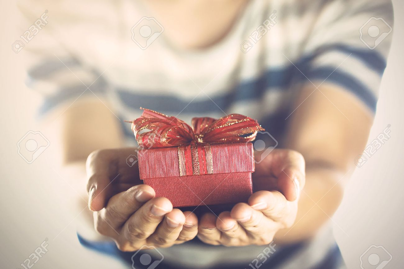 Young man giving and presenting a gift to someone. Stock Photo - 54759160