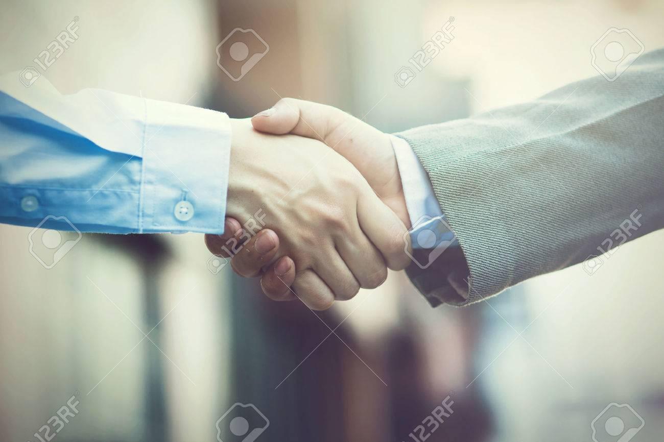 Business handshake. Two businessman shaking hands (Vintage tone) - 54745382