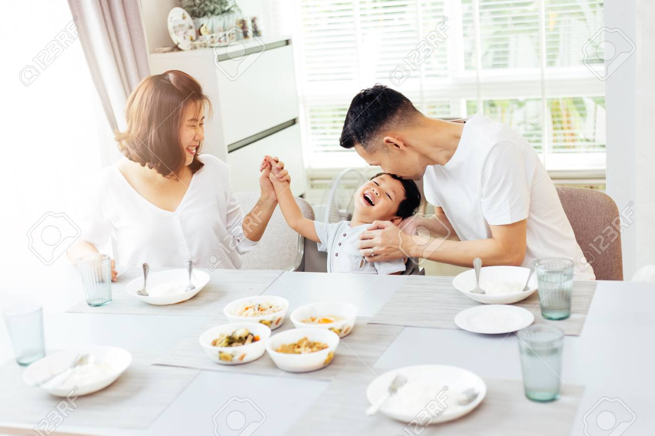 Happy Asian family of father, mother and son playing and laughing while having dinner - 100021275
