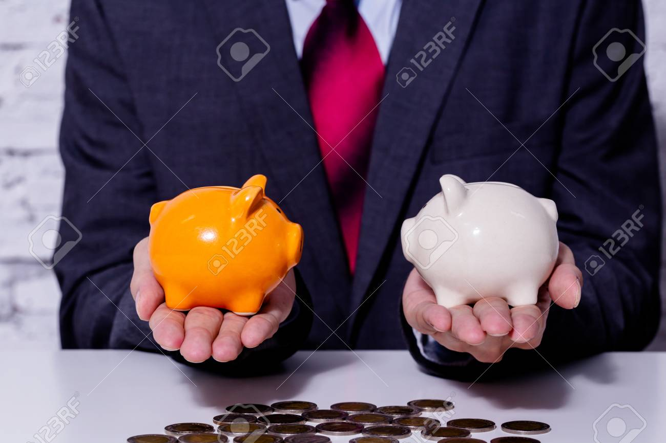 Businessman making a comparison and difference between each money piggy bank - finance issue comparison concept - 102747286