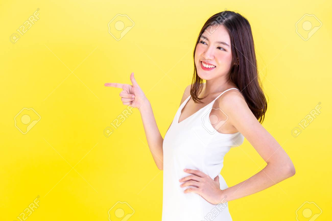 Asian cute woman pointing hands to empty copy space and posing arms akimbo isolated on yellow background - 105276733