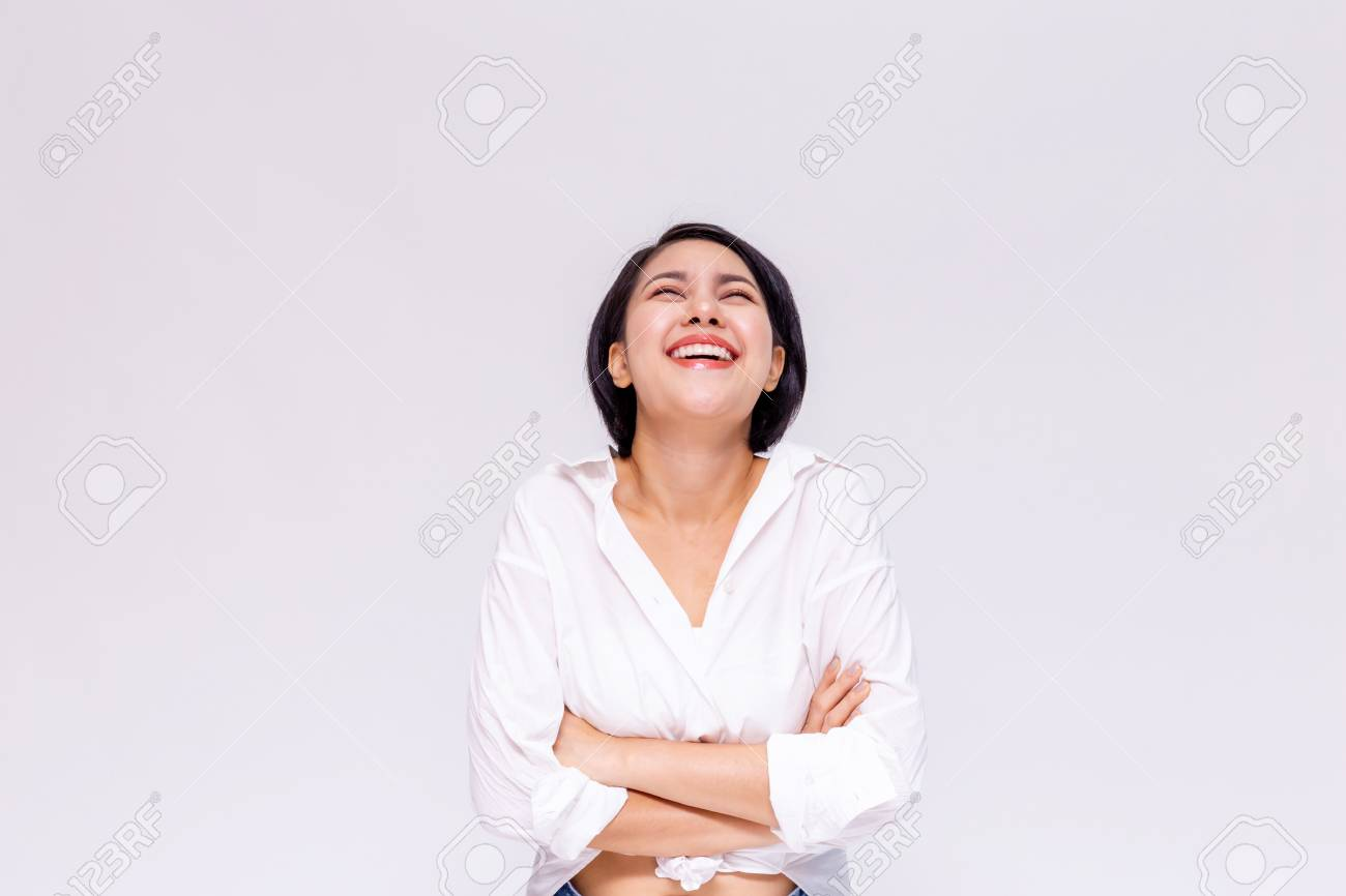 Young beautiful and confident Asian girl with short hair arms crossed with joy and happiness in white isolated background - 105388987