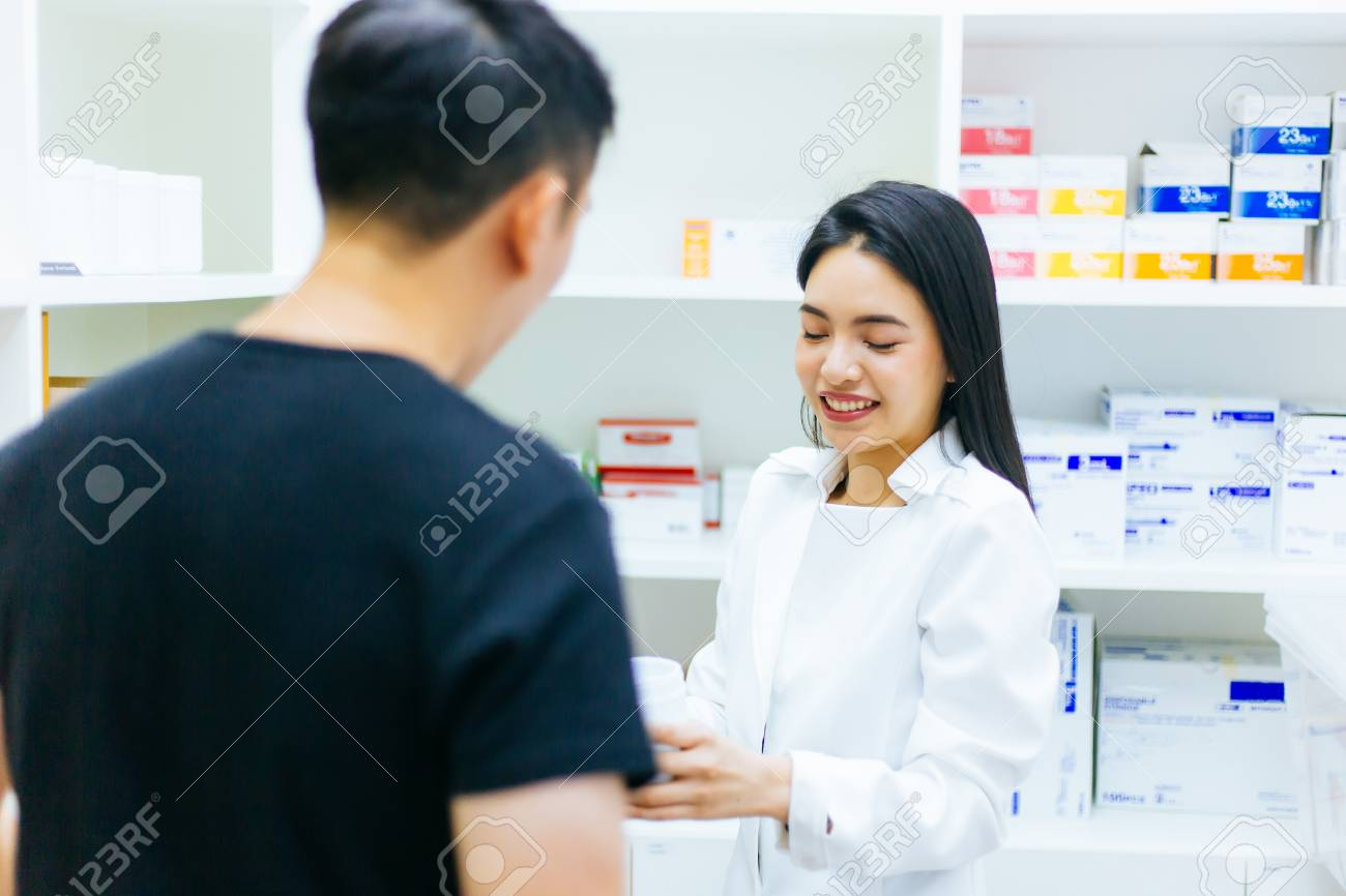 Asian female pharmacist doctor in professional gown explaining and giving advice with male client in drugstore shop - 105455382