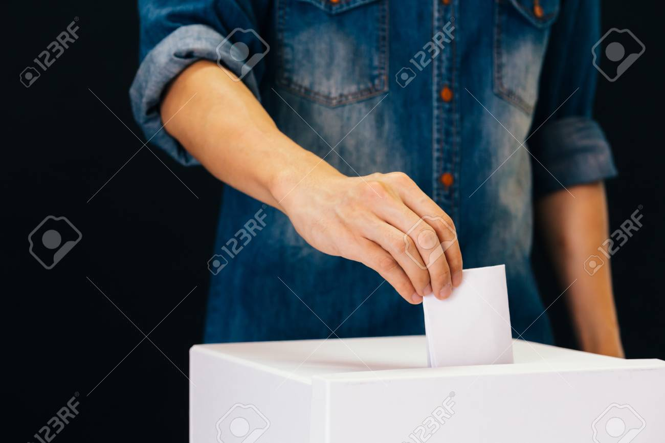 Front view of person holding ballot paper casting vote at a polling station for election vote in black background - 115237591