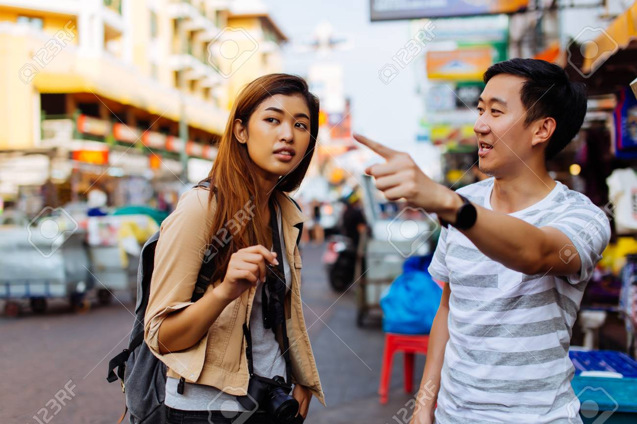 Young female tourist asking for directions and help from local people in Bangkok, Thailand - 120427495