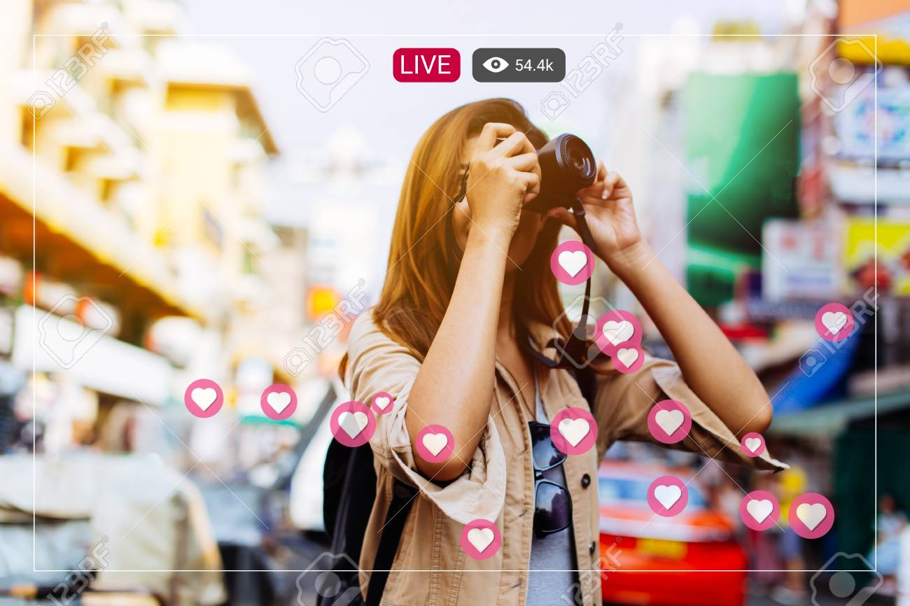 Young Asian female tourist woman with smile holding a camera and taking photos in Bangkok, Thailand while travelling in Southeast Asia - 121074349