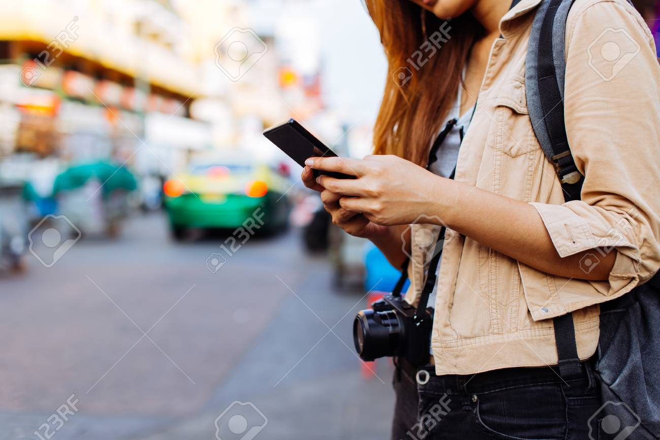 Young Asian female tourist woman using a mobile phone in Bangkok, Thailand. Calling a cab or finding information during traveling concept - 121075048