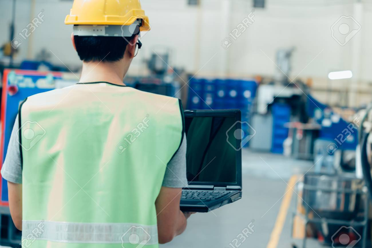 Asian male Industrial engineer in hardhat works with laptop in safety jacket at heavy industry factory. Processing plastic injection molding industry - 124609807