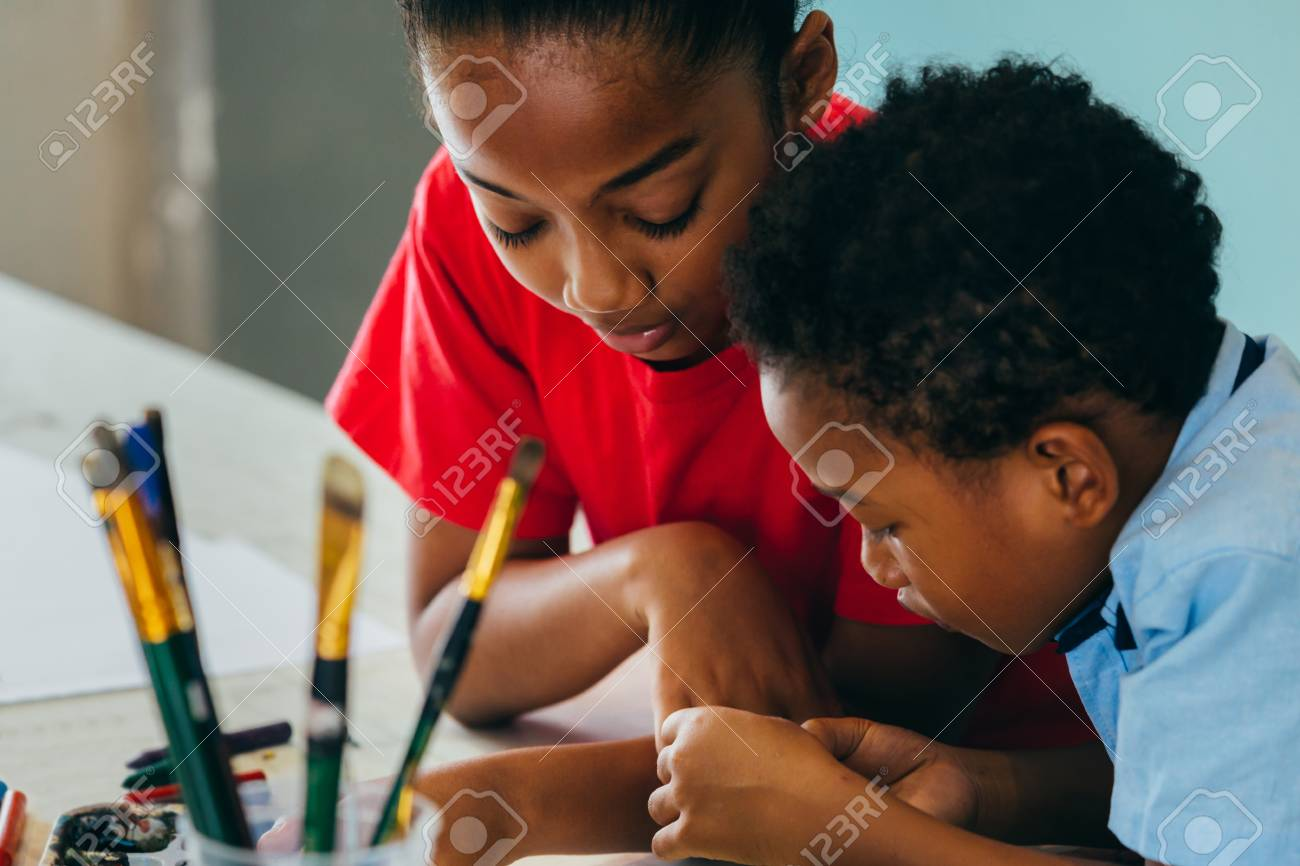 Closeup of elementary African American kids creatively drawing and painting with brushes and crayon - children creative education concept - 124612054