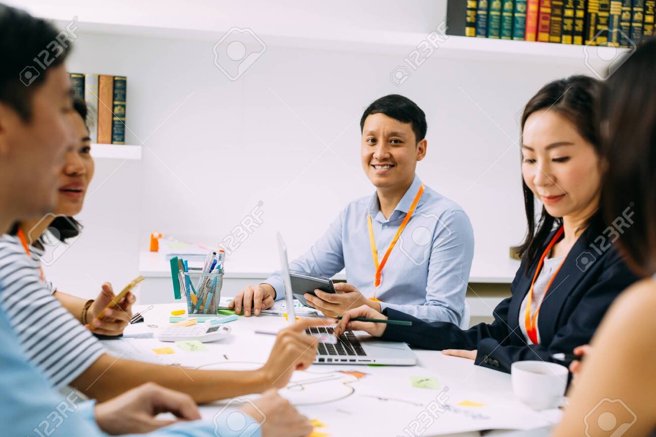 Asian mature business man smiling and looking at camera while sitting in meeting with other business men and women. Smart middle age guy having discussion. - 129208521