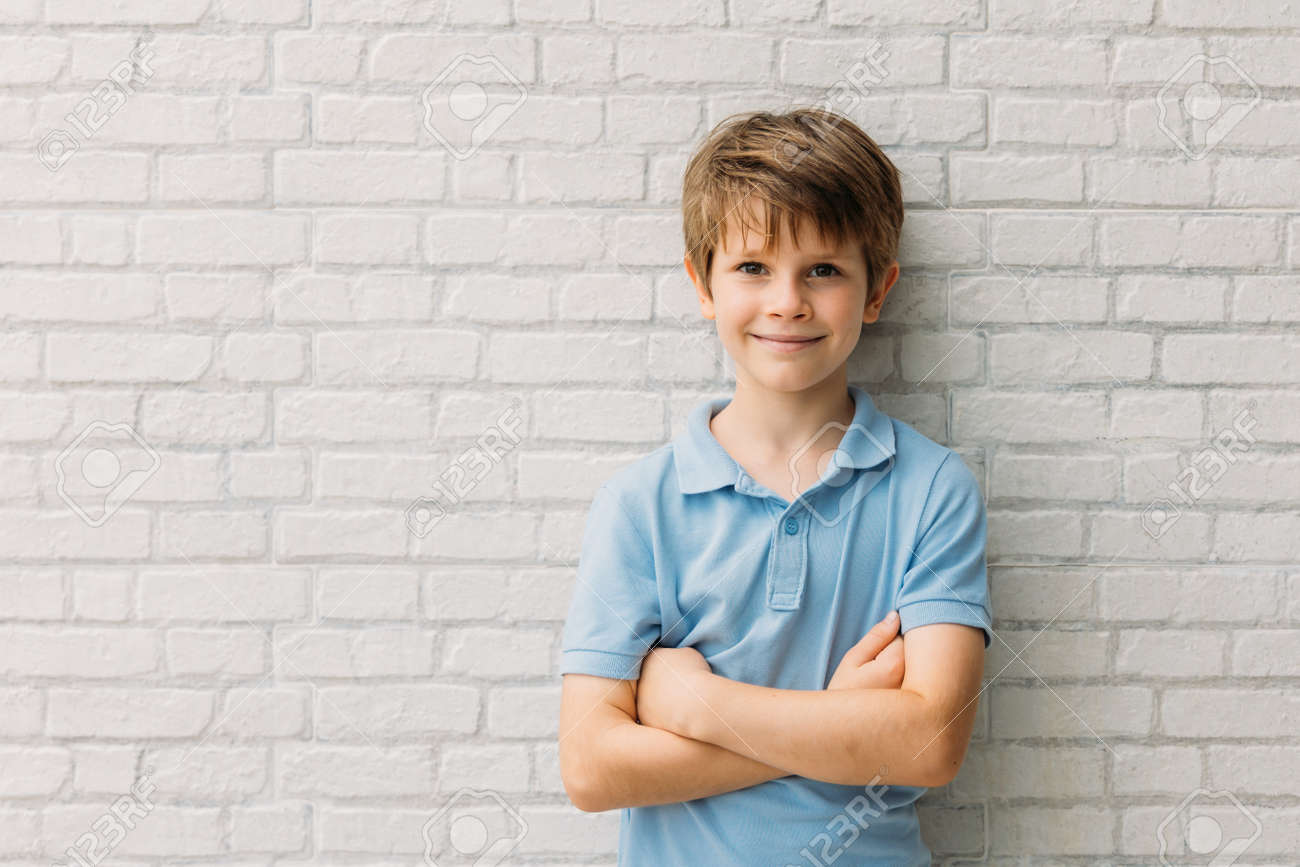 Portrait of happy young caucasian boy in casual outfit with arms crossed isolated over white bricks background smiling and looking at camera - 167037671