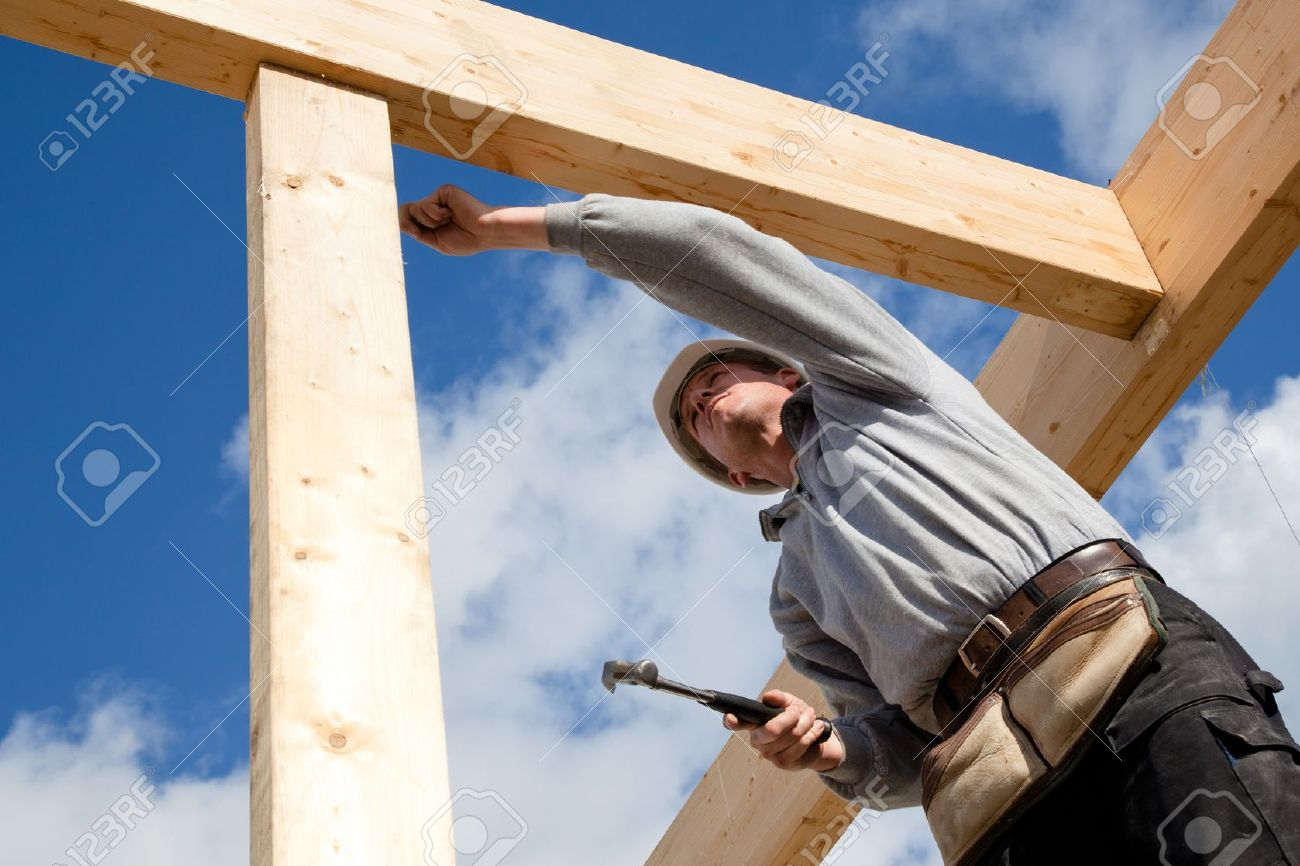 construction worker at work with wooden roof construction - 17900979