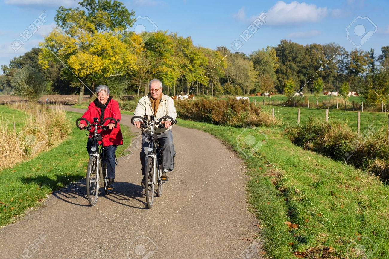 Senior man and woman on bicycles on a dutch countryroad - 30668695