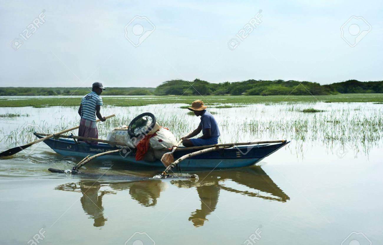 Bentota, Sri Lanka - 13, 2001: Two Sri Lankan men  floating in  the boat  by the small river. Stock Photo - 10911563