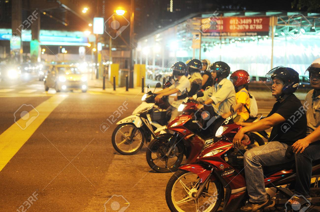 KUALA LUMPUR, MALAYSIA - MARCH 16, 2012: Motorcyclist on the road in Kuala Lumpur. The road network system in Kuala Lumpur is similar to the city road network system in major Chinese cites - 28661585