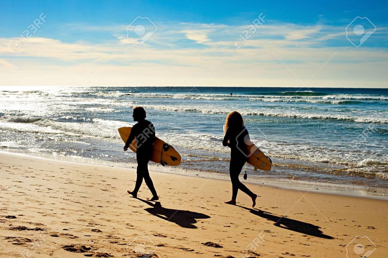 オーシャン ビーチの上を歩いてサーファーのカップル サグレス