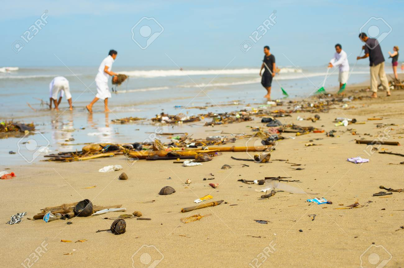 Group of people cleaning up beach from the garbage and plastic waste. - 117215981
