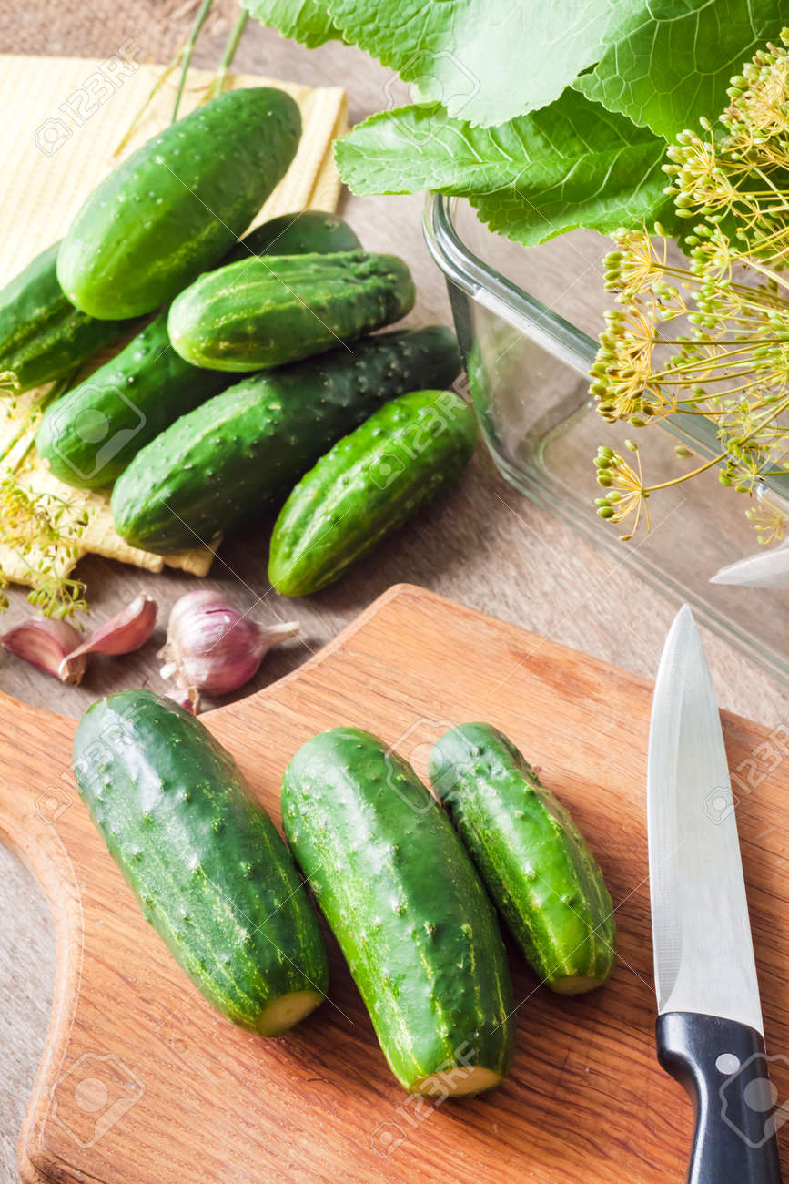 Fresh cucumbers on wooden board prepared for pickling in glass container - 124074971
