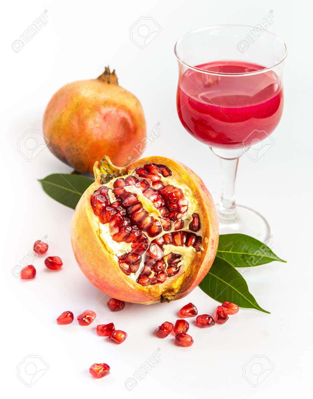 Ripe pomegranate with pomegranate juice in a glass on a white background. - 157798969