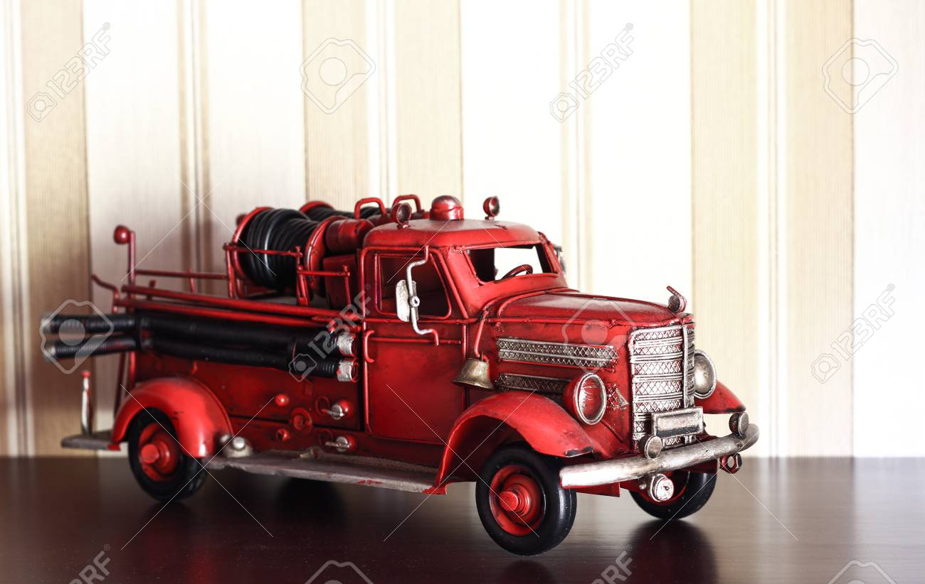 Car Plastic Model Of An Old Classic Red Fire Truck On A Stripped