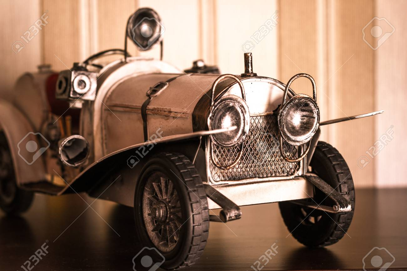White Classic Car Model Toy Over Brown Stripped Wallpaper Retro