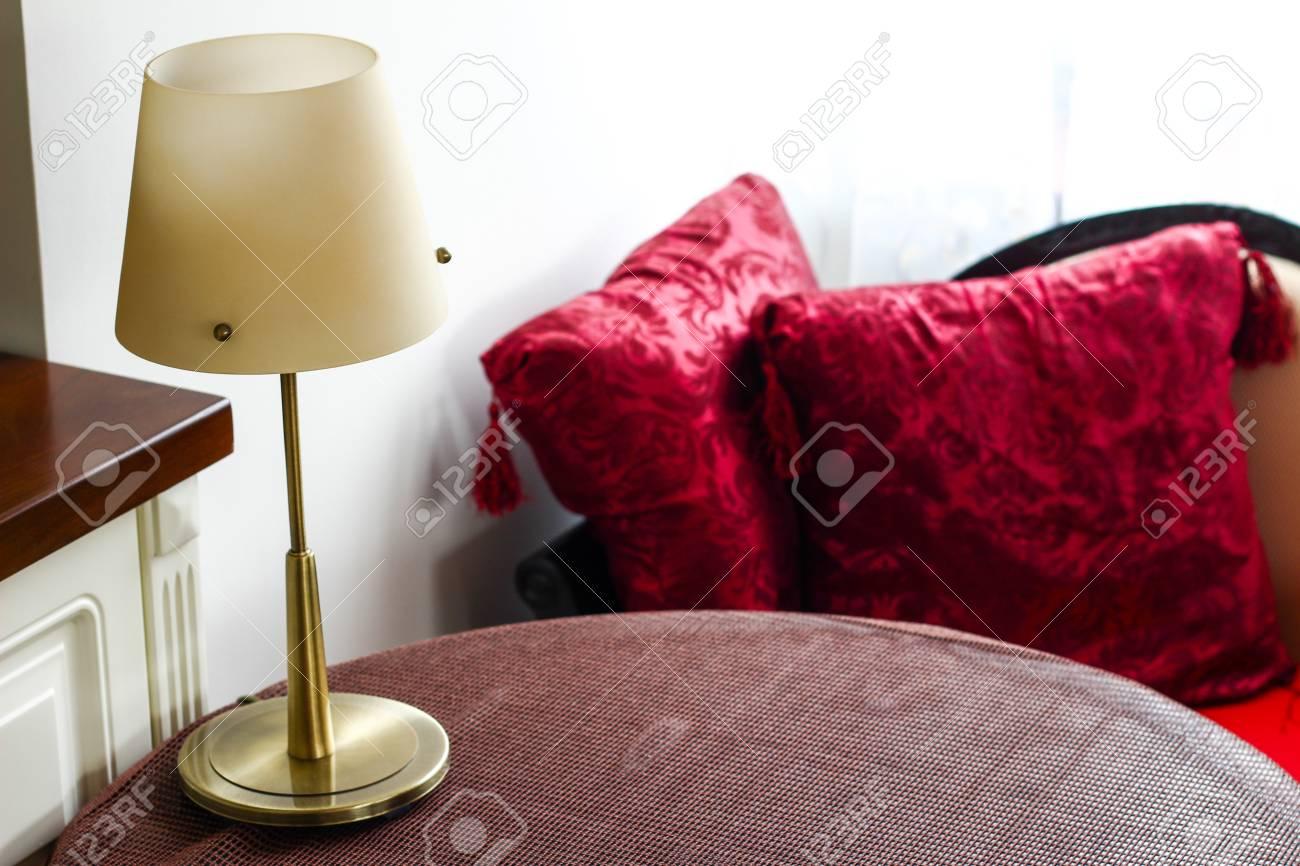 Habitación con una mesa con mantel marrón, lámpara y cojines rojos