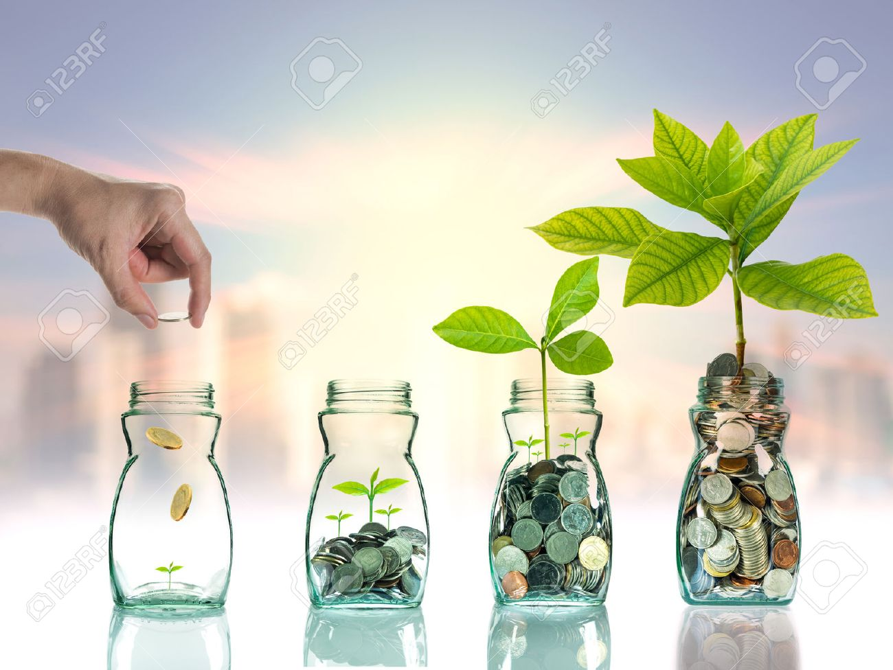 Hand putting mix coins and seed in clear bottle on cityscape photo blurred cityscape ,Business investment growth concept - 45039067