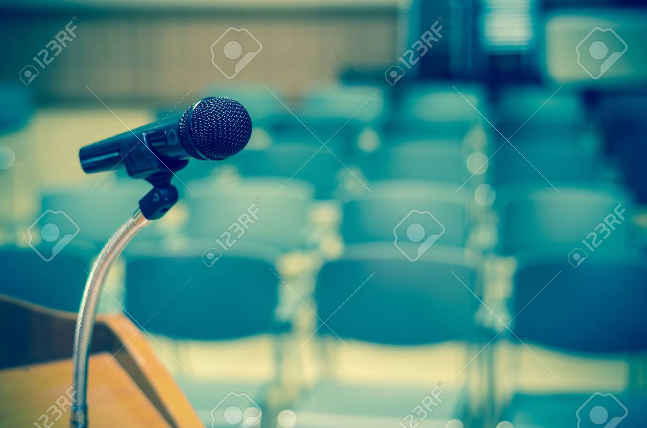 Microphone on the speech podium over the Abstract blurred photo of conference hall or seminar room background - 52460620