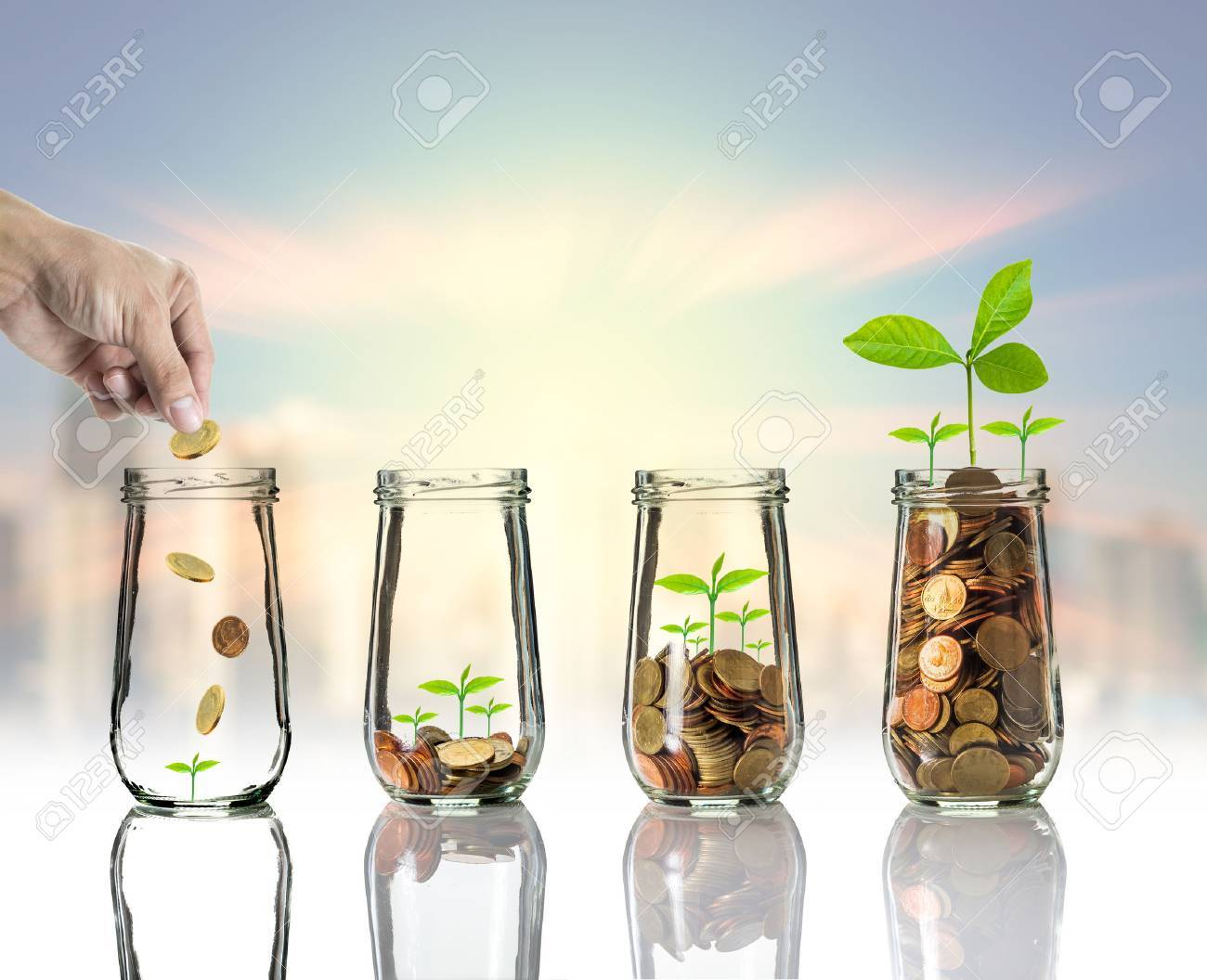 Hand putting Gold coins and seed in clear bottle on cityscape photo blurred cityscape background,Business investment growth concept - 55319421