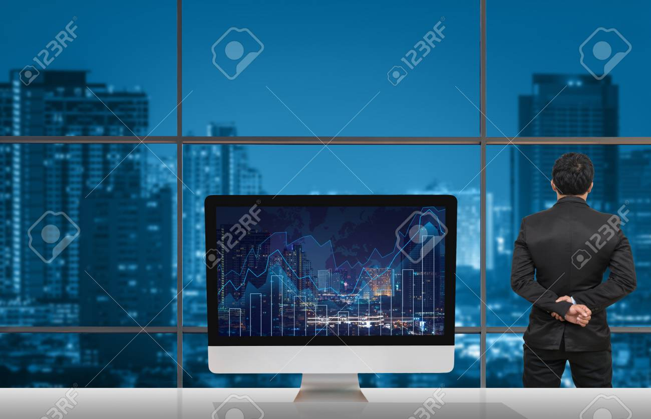 Back side of businessman looking at citiy out off windows glass back side of businessman looking at citiy out off windows glass with computer show trading graph gumiabroncs Images