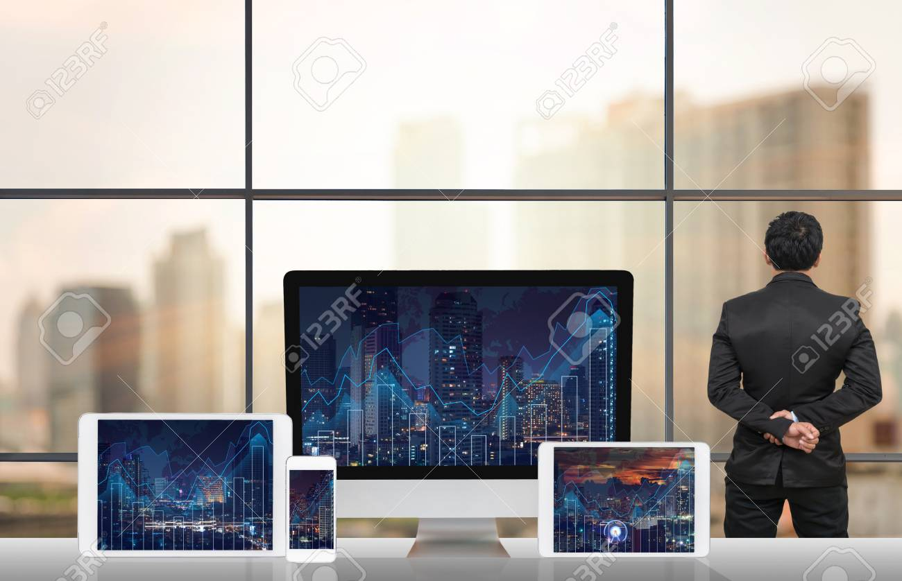 Back side of businessman looking at city out off windows glass with back side of businessman looking at city out off windows glass with computer set show trading graph on the cityscape and world map background on the table gumiabroncs Images