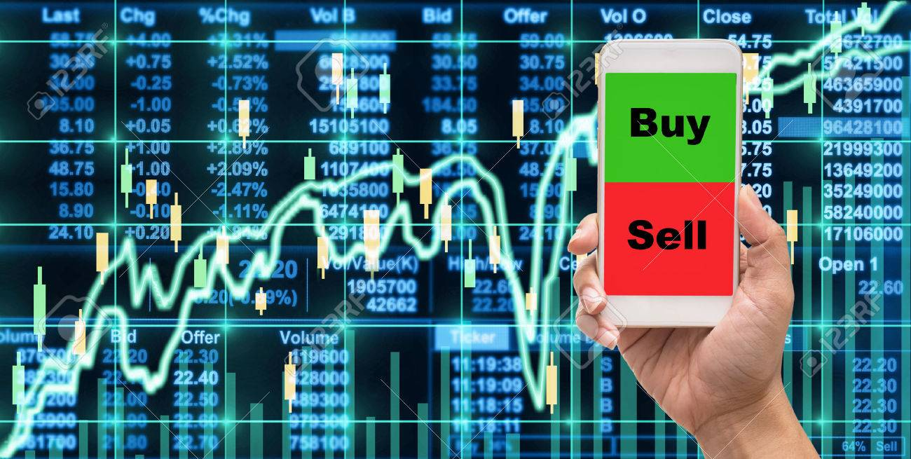 Female hand holding mobile phone touch screen showing buy and sell over the Stock market chart,Closeup Stock market exchange data on LED display, business trading concept - 70758895