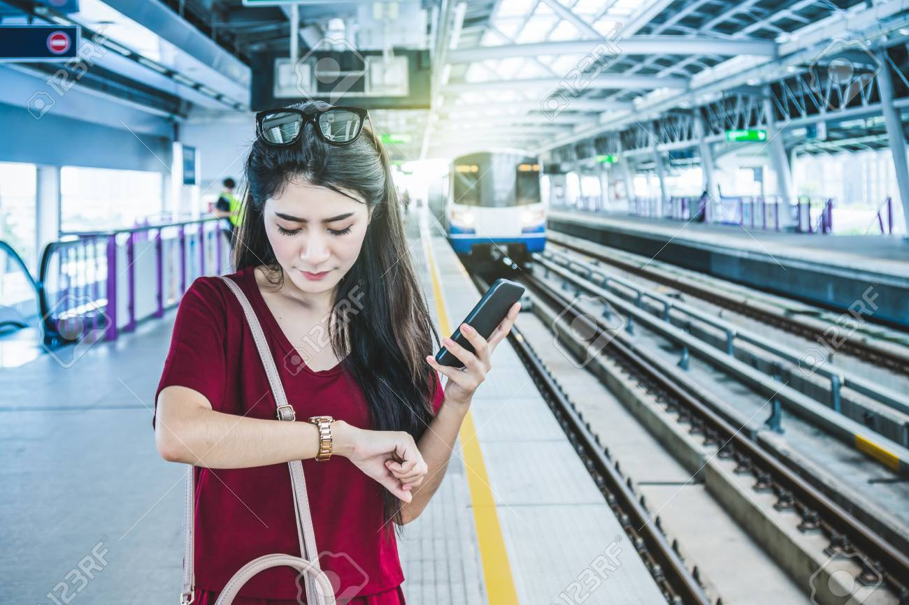 Asian woman passenger with casual suit watching the clock and waiting in the BTS Skytrain rails or MRT subway for travel in the big city, lifestyle and transportation concept - 87817584