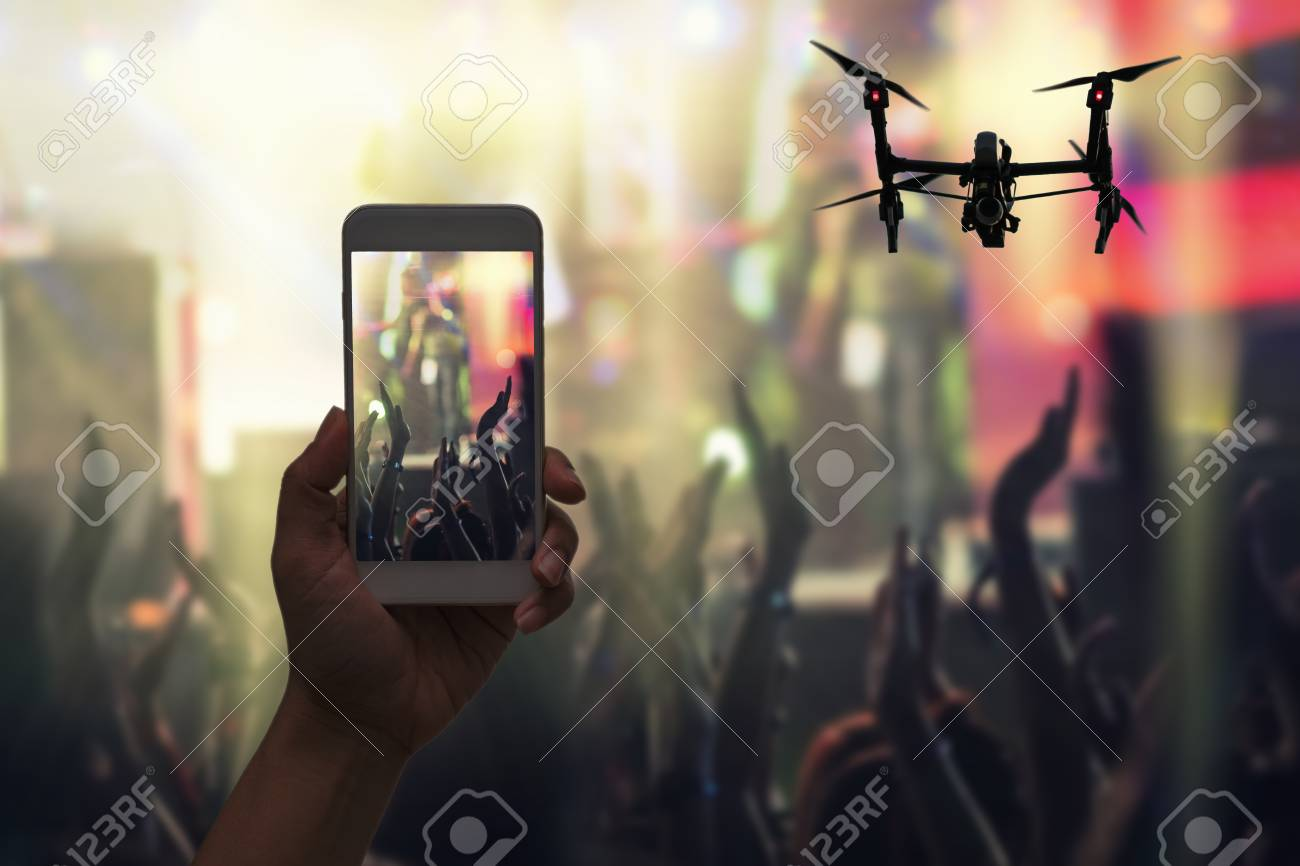 Female hand holding mobile smart phone and Drone flying taking