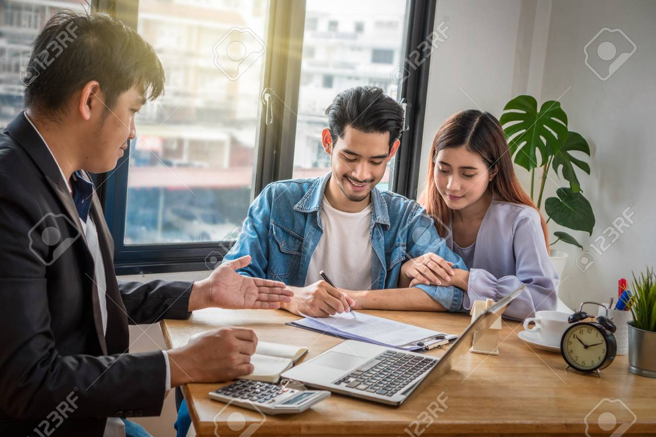 Asian young couple sign contact of house purchase or rental whihc have Sale representative offer the condition in document on the working space table in new house,Moving and House Hunting concept, - 108742372