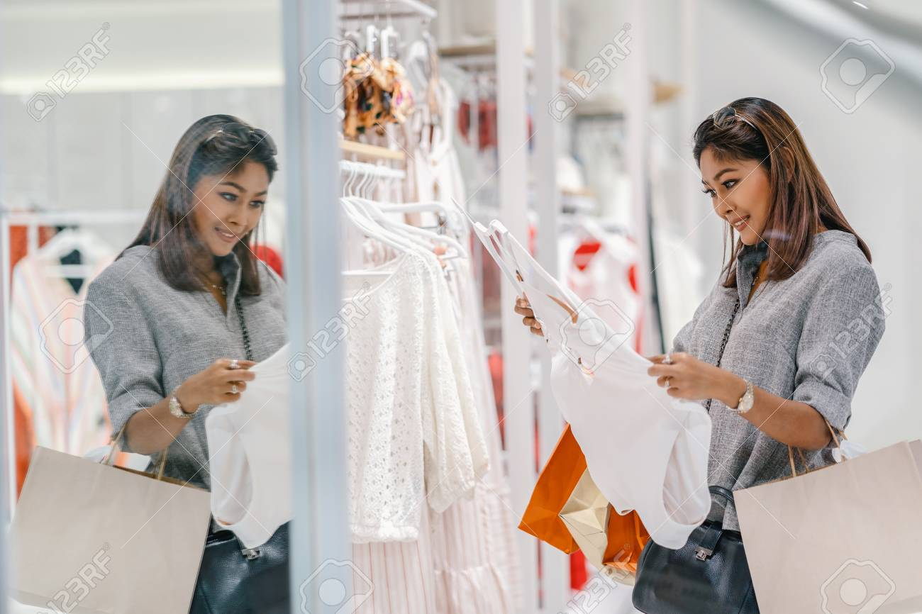 Asian woman looking and choosing the underwear in store shop with happy action at department center - 110363641