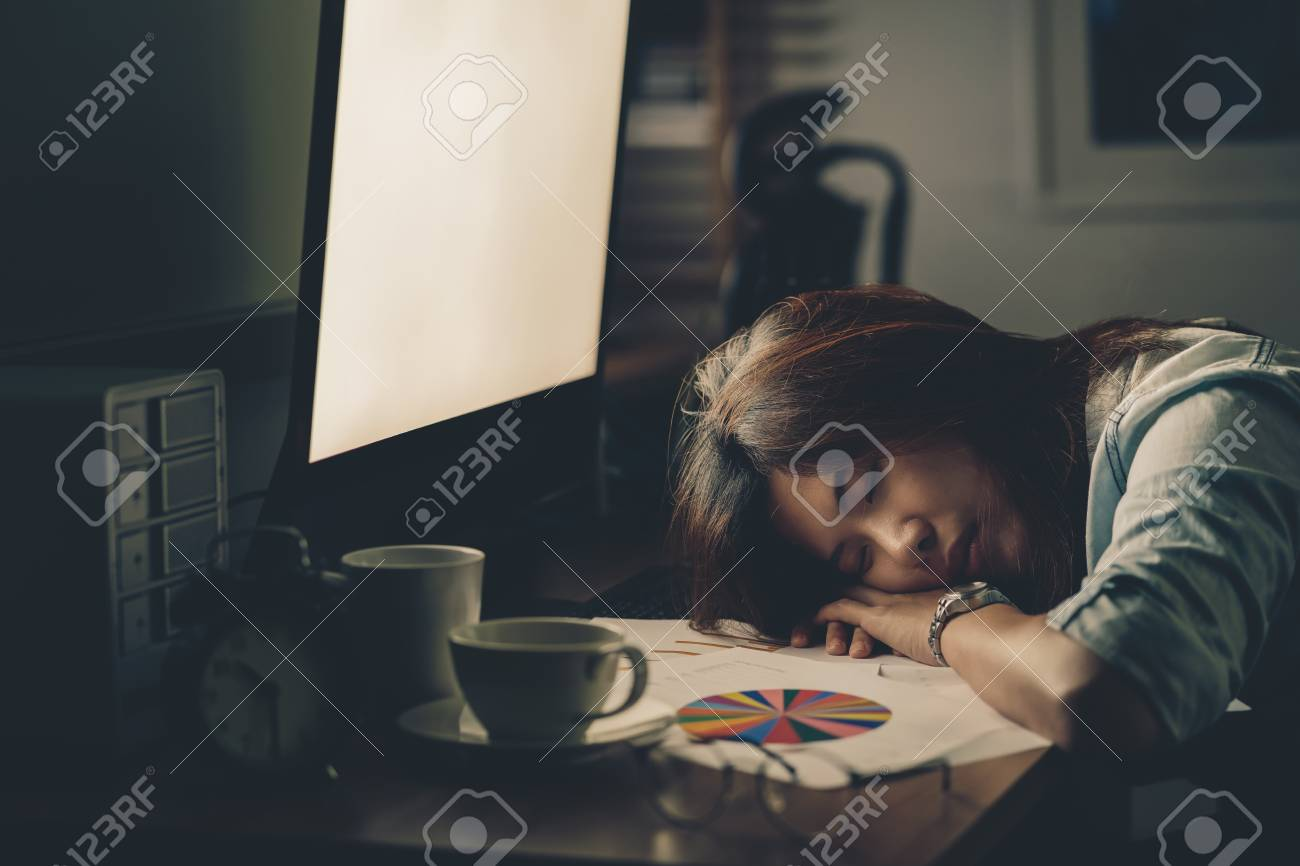 Portrait of Asian Businesswoman hard working and sleeping on the table with front of computer desktop in workplace at late with serious action, Work hard and too late concept - 118618729