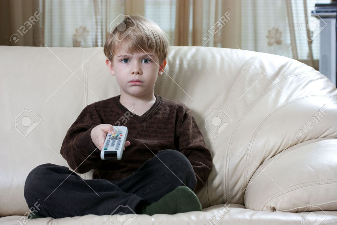 cute little boy sitting on the sofa and watching tv with a remote control - 6247930