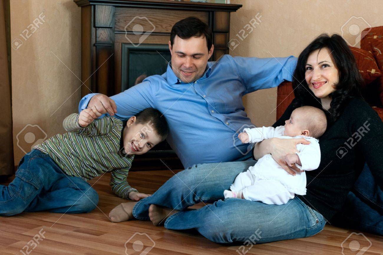 happy family home: father, mother, son and baby lying on the floor and playing Stock Photo - 6635462