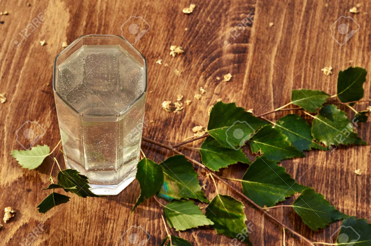 Glasses of birch sap juice birch branches on wooden table background