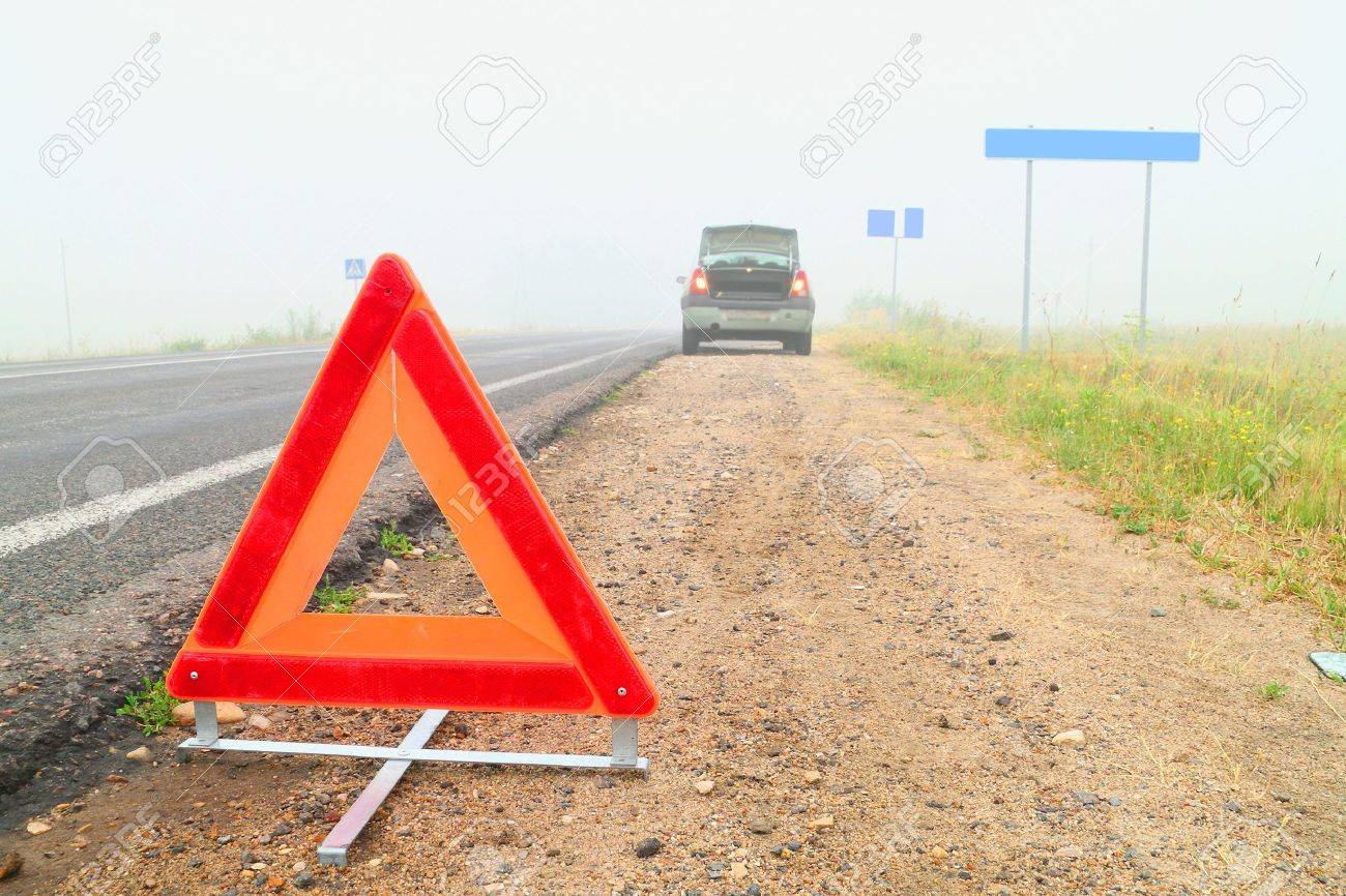 The image of emergency stop sign under the foreground and part of blurred broken car under background. Focus is under the sign. Stock Photo - 7974721
